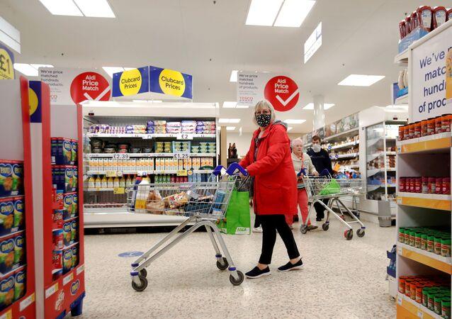 Mulher usando máscara facial empurra carrinho de compras em um supermercado Tesco em Hatfield, Reino Unido, 6 de outubro de 2020