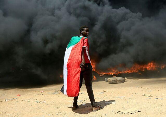 Manifestante com bandeira do Sudão na frente de uma pilha de pneus em chamas durante protestos em Cartum, 21 de outubro de 2021