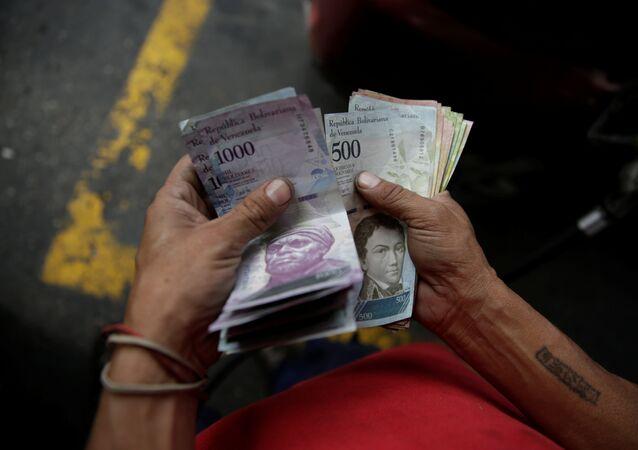 Trabalhador contando bolívares venezuelanos em Caracas