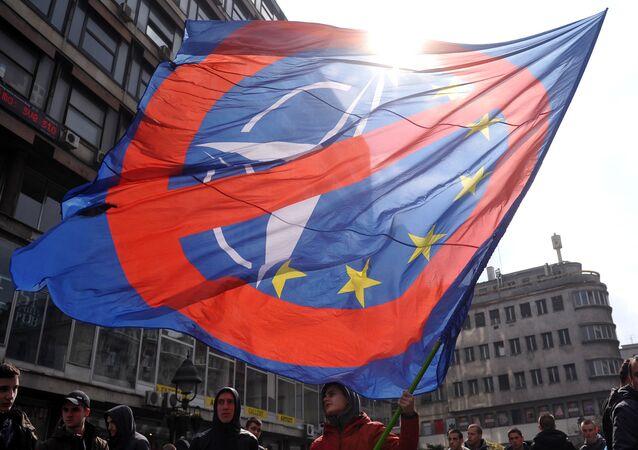 Homem acena com uma bandeira contra a OTAN e União Europeia em Belgrado, Sérvia, 27 de março de 2016