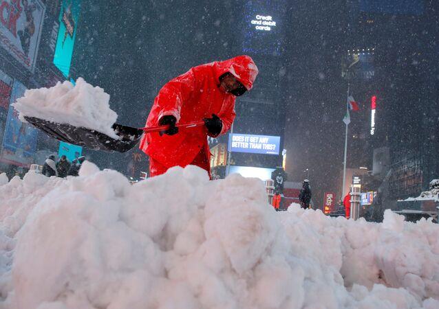 Trabalhador municipal desbloqueia a rua tomada pela neve em Manhattan, Nova York
