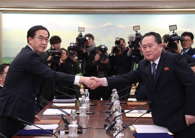 Ministro da Unificação da Coreia do Sul, Cho Myung-gyun (à esquerda), e líder da delegação norte-coreana Ri Son-gwon apertando as mãos durante negociações bilaterais na zona desmilitarizada, 9 de janeiro de 2017