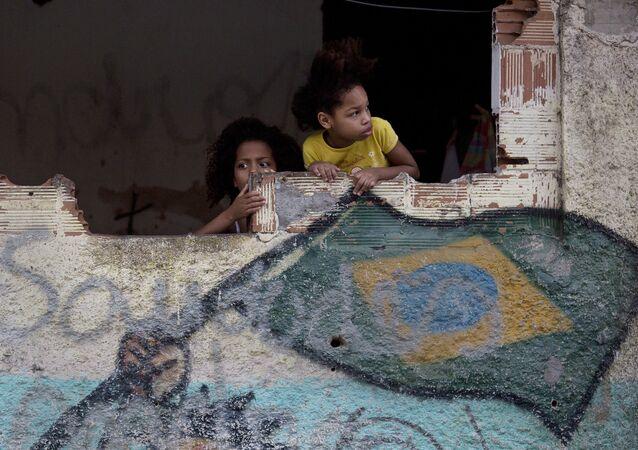 Garotas na favela de Manquinhos, no Rio de Janeiro, Brasil, assistem manifestação em prol da paz, exigindo o fim da violência entre traficantes e policiais.