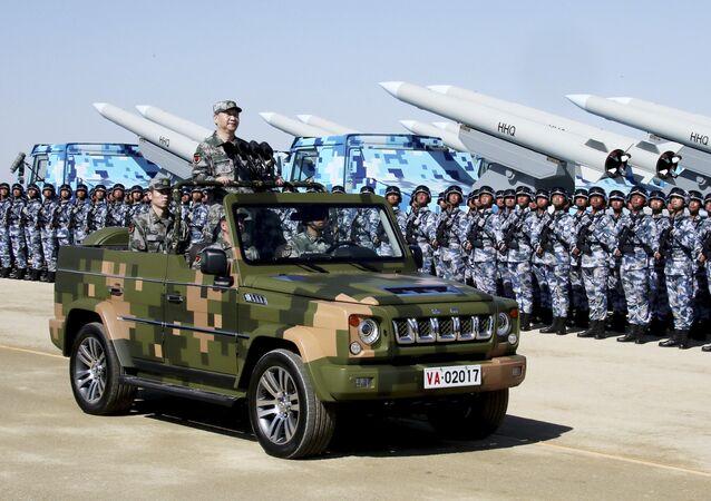 Nesta foto divulgada pela Agência de Notícias Xinhua, o presidente chinês, Xi Jinping, sobe em jipe militar enquanto inspeciona as tropas do Exército de Libertação do Povo durante uma parada militar para comemorar o 90º aniversário da fundação das tropas (junho de 2017).
