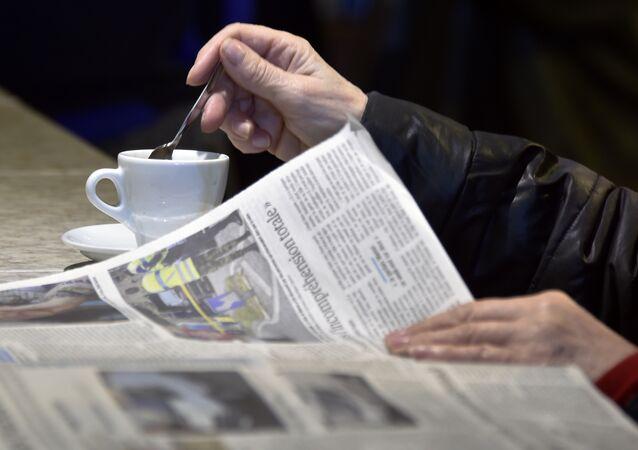Homem lê um jornal francês tomando o café.