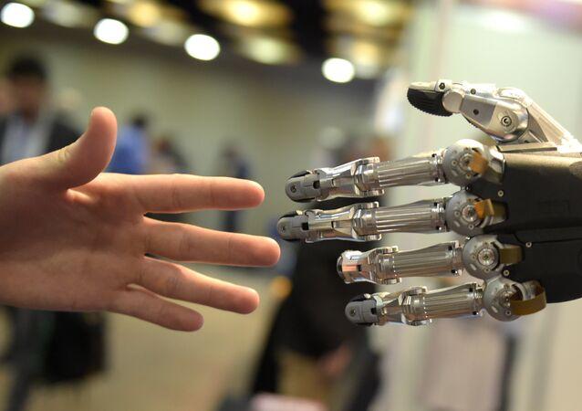 Homem tentando tocar mão robótica na Conferência Internacional de Robôs Humanoides em Madri (foto de arquivo)