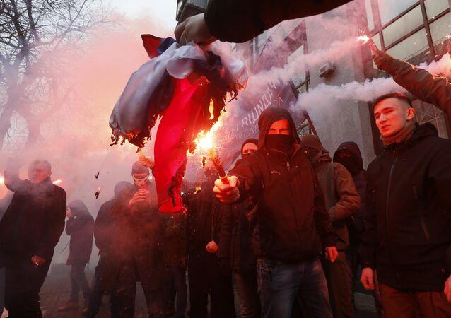 Ativistas e apoiantes de partidos e movimentos nacionalistas ucranianos queimam a bandeira do Estado russo, que foi confiscada do escritório do Centro de Ciência e Cultura da Rússia durante um protesto em Kiev em 17 de fevereiro de 2018