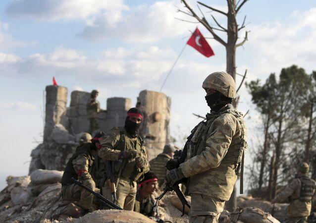 Combatentes pró-Turquia e tropas turcas na colina que separa Afrin da cidade turca de Azaz