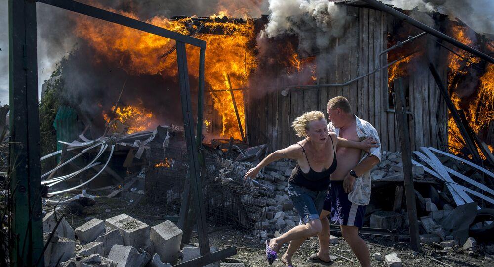 Residentes fogem da sua casa destruída pelo exército da Ucrânia, região de Lugansk, 2014