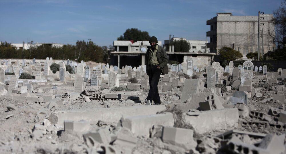 Homem caminha por um cemitério em um bairro fortemente danificado por ataques aéreos na aldeia de Deir al-Asafir, na região rebelde de Ghouta Oriental, arredores de Damasco (Arquivo)