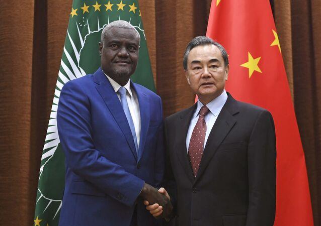 Presidente da Comissão da União Africana Moussa Faki Mahamat, à esquerda, posa ao lado do ministro chinês das Relações Exteriores, Wang Wi, à direita. Encontro aconteceu em Pequim, no dia 8 de fevereiro de 2018.