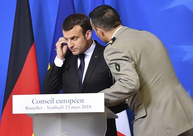O presidente da França, Emmanuel Macron, escuta adido militar durante cúpula da UE em Bruxelas em 23 de março de 2018