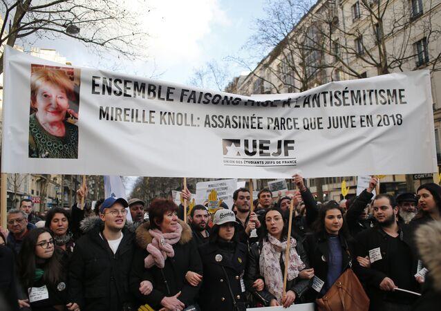 Pessoas carregando um cartaz com uma foto de Mireille Knoll enquanto marcham em silêncio durante uma amnifestação contra o anti-semitismo em Paris, França.