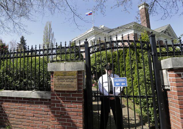 Enquanto a bandeira russa permanece hasteada, um oficial de segurança está atrás dos portões da residência antiga do cônsul russo, 25 de abril de 2018, Seattle, EUA
