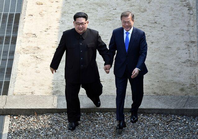 Líder norte-coreano Kim Jong-un e seu homólogo sul-coreano Moon Jae-in atravessam a linha que demarca a zona desmilitarizada na aldeia fronteiriça de Panmunjom, 27 de abril de 2018