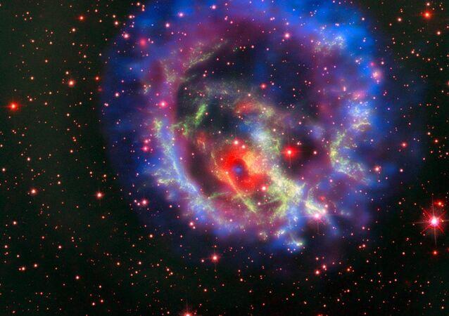 Esta nova imagem criada a partir de imagens de telescópios no solo e no espaço conta a história da caça por um objeto desaparecido escondido em meio a um emaranhado complexo de filamentos gasosos em uma de nossas galáxias vizinhas, a Pequena Nuvem de Magalhães. A imagem vem do Telescópio Espacial Hubble da NASA / ESA e revela partículas de gás formando supernova remanescente 1E 0102.2-7219 em verde. O anel vermelho com um centro escuro é do instrumento MUSE no Very Large Telescope do ESO e as imagens azuis e roxas são do Observatório Chandra X-Ray da NASA. A mancha azul no centro do anel vermelho é uma estrela de nêutrons isolada com um campo magnético fraco, o primeiro identificado fora da Via Láctea.