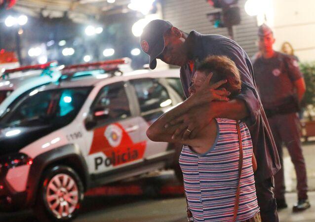 Agente federal acalmando uma mulher perto do local do incêndio em São Paulo, 1º de maio de 2018