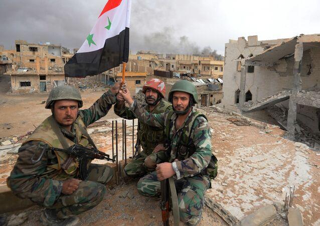 Soldados do Exército sírio com bandeira da Síria se alegram com a libertação de Palmira