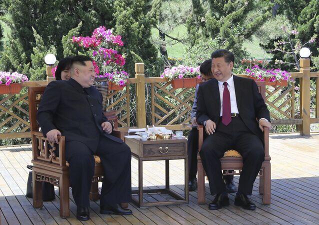 Presidente chinês, Xi Jinping (à direita), falando com o líder norte-coreano, Kim Jong-un (à esquerda) em Dalian, China