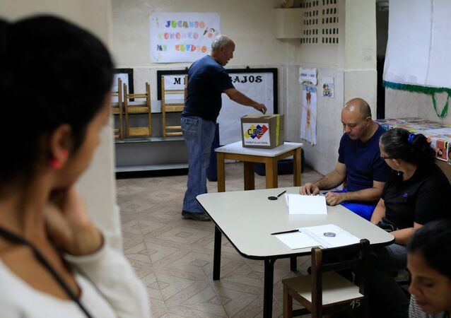 Um venezuelano joga seu voto em uma seção de votação durante a eleição presidencial em Caracas, Venezuela.