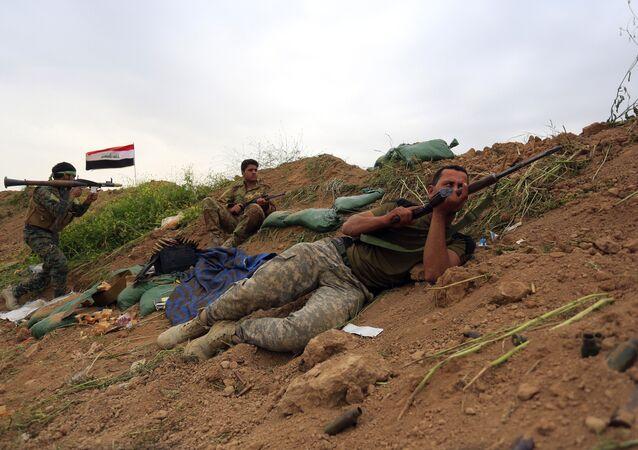 Forças de segurança iraquianas e forças de mobilização popular aliadas assumem posições de combate durante uma operação militar para recuperar o controle da cidade de Besher, subúrbios da cidade de Kirkuk, rica em petróleo.