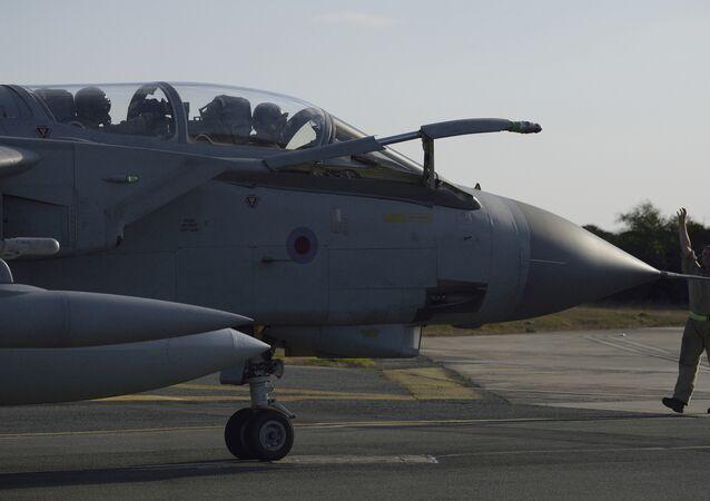 Oficial acenando para pilotos de um avião da Força Aérea Real Tornado