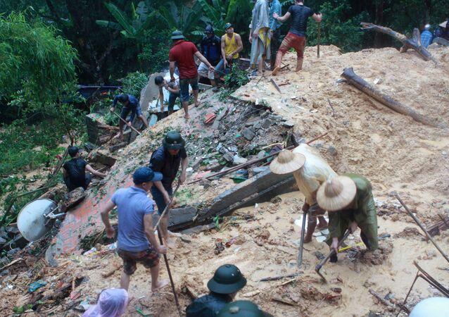 Pessoas fazem buscas sobre um deslizamento de terra causado por fortes enchentes no Vietnã. (Foto de Arquvo)