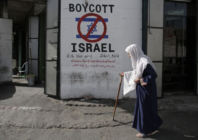 A Palestinian woman walks past a mural calling people to boycott Israeli goods in the al-Azzeh refugee camp near the West Bank city of Bethlehem on September 17, 2014