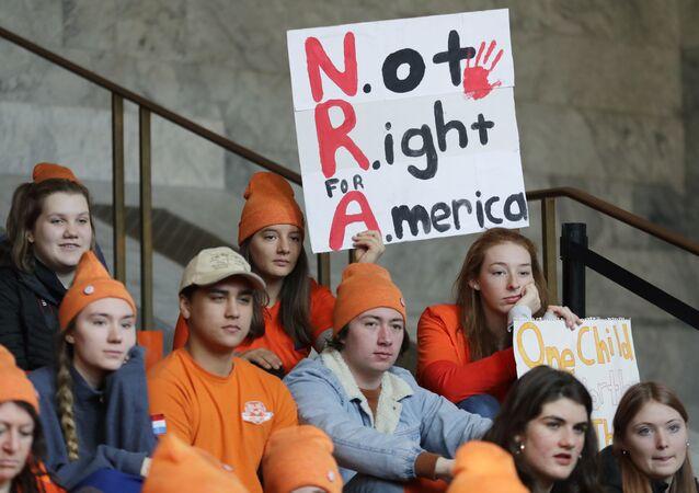 Estudante em Seattle segura uma placa que diz NRA - Not Right for America (NRA - Não é o melhor para América, em tradução livre) enquanto participa de uma manifestação contra a violência armada.