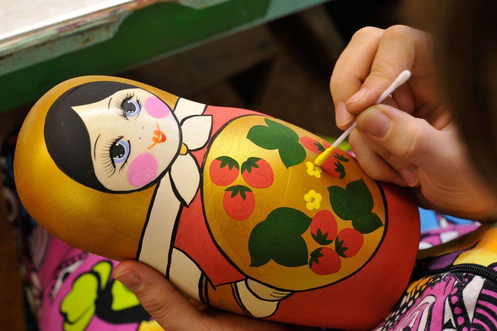 Artesã pintando uma matryoshka à mão