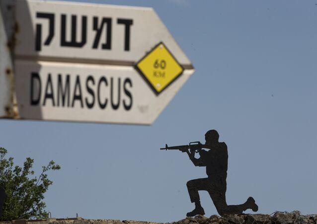 Escultura de militar israelense perto de uma seta indicando as distâncias de Bagdá e Damasco perto de um posto militar nas Colinas de Golã