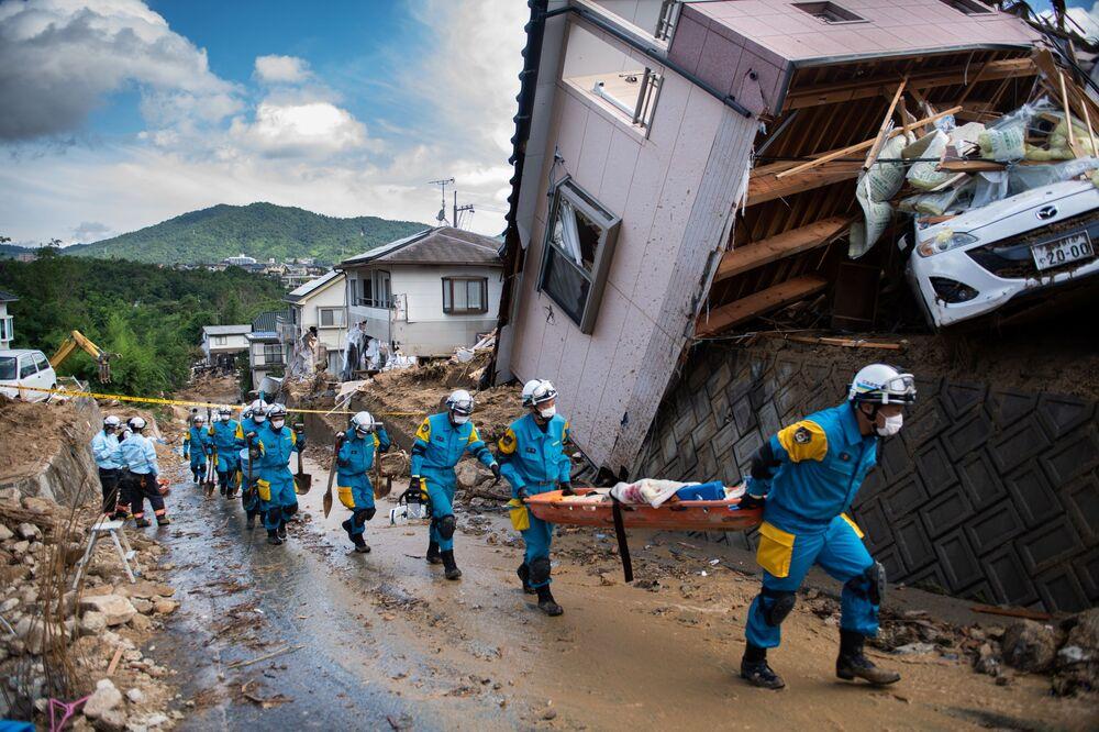 Bombeiros e policiais junto às moradias desmoronadas na sequência de aguaceiros fortes no Japão