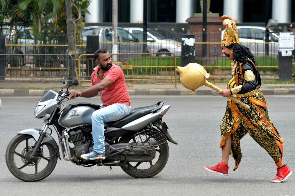 Artista vestido de deus da morte hinduísta Enma, junto a um motoqueiro, na Índia