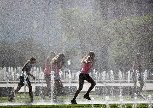 Meninas correm através de fontes em um dia quente de verão em Berlim, Alemanha (arquivo)