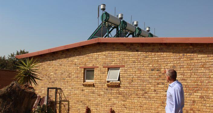 Residente de Kleinfontein mostra painéis solares em sua moradia alugada