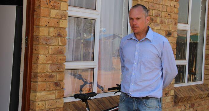 Residente de Kleinfontein em frente de sua moradia alugada