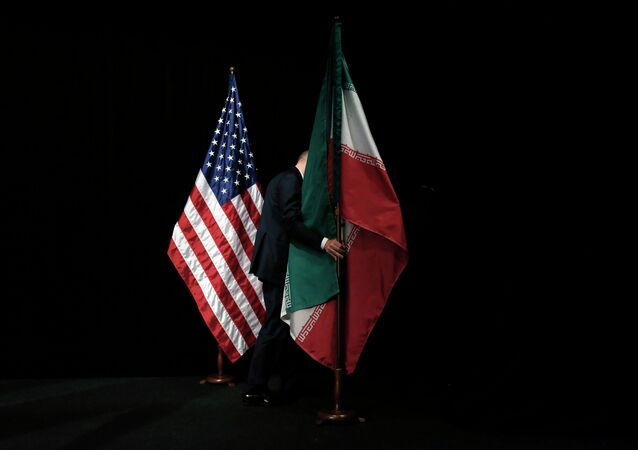 Um homem remove a bandeira iraniana do palco depois de uma foto de grupo com ministros das Relações Exteriores e representantes dos Estados Unidos, Irã, China, Rússia, Grã-Bretanha, Alemanha, França e União Europeia durante as conversações nucleares do Irã no Centro Internacional de Viena em Viena , Áustria (arquivo)