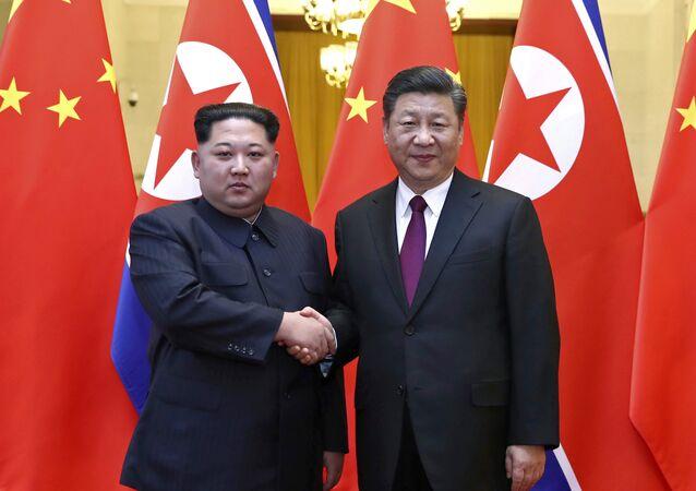O líder norte-coreano Kim Jong-un, à esquerda, e o presidente chinês Xi Jinping apertam as mãos durante encontro em Pequim.