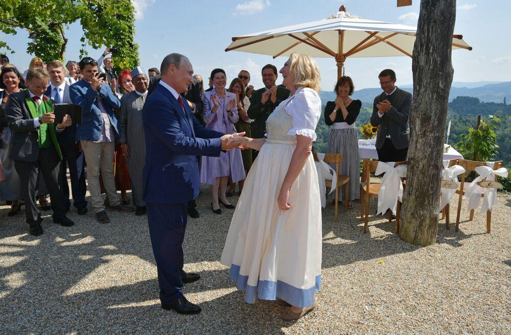 O presidente da Rússia, Vladimir Putin, dança com a chanceler da Áustria, Karin Kneissl, no seu casamento com o empresário Wolfgang Meilinger