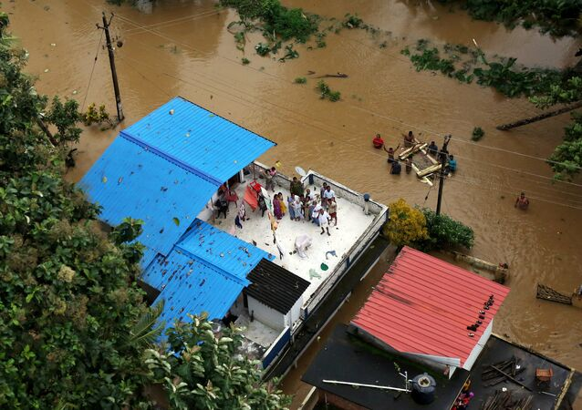Pessoas esperam por ajuda sobre um telhado após enchente no estado indiano de Kerala