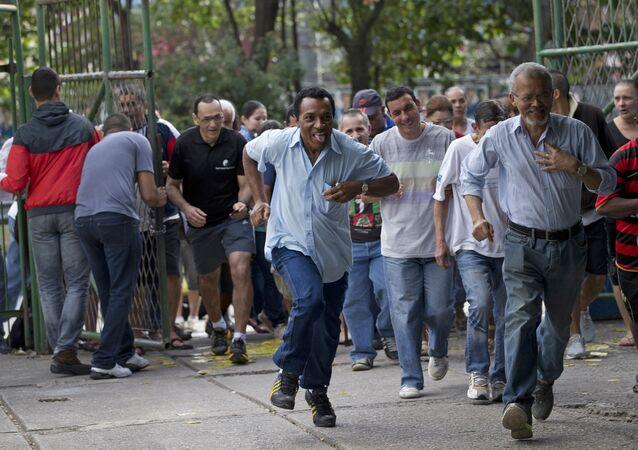 Homens correm para vota assim que os portões de um colégio eleitoral se abriram na favela da Rocinha, no Rio de Janeiro, durante as eleições de 2014.