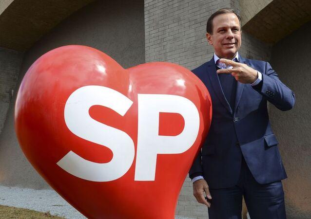 João Doria posa ao lado da logomarca da Prefeitura de São Paulo