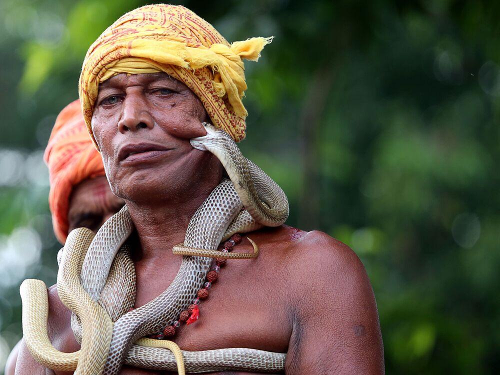 Encantador de serpentes indiano participa do festival dedicado à festa Maa Mansa Puja, no estado de Jharkhand
