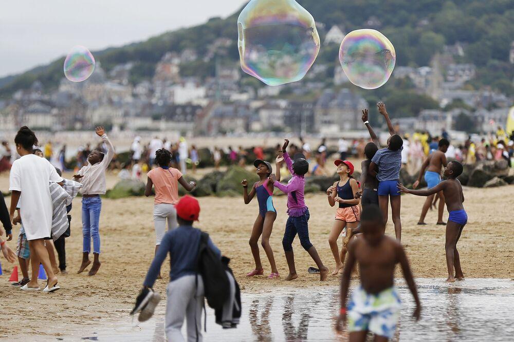 """Crianças brincam na praia de Cabourg, na França, no âmbito de uma campanha """"Esquecidos pelas Férias"""" destinada a providenciar lazer às crianças cujas famílias não podem se dar ao luxo de viajar"""