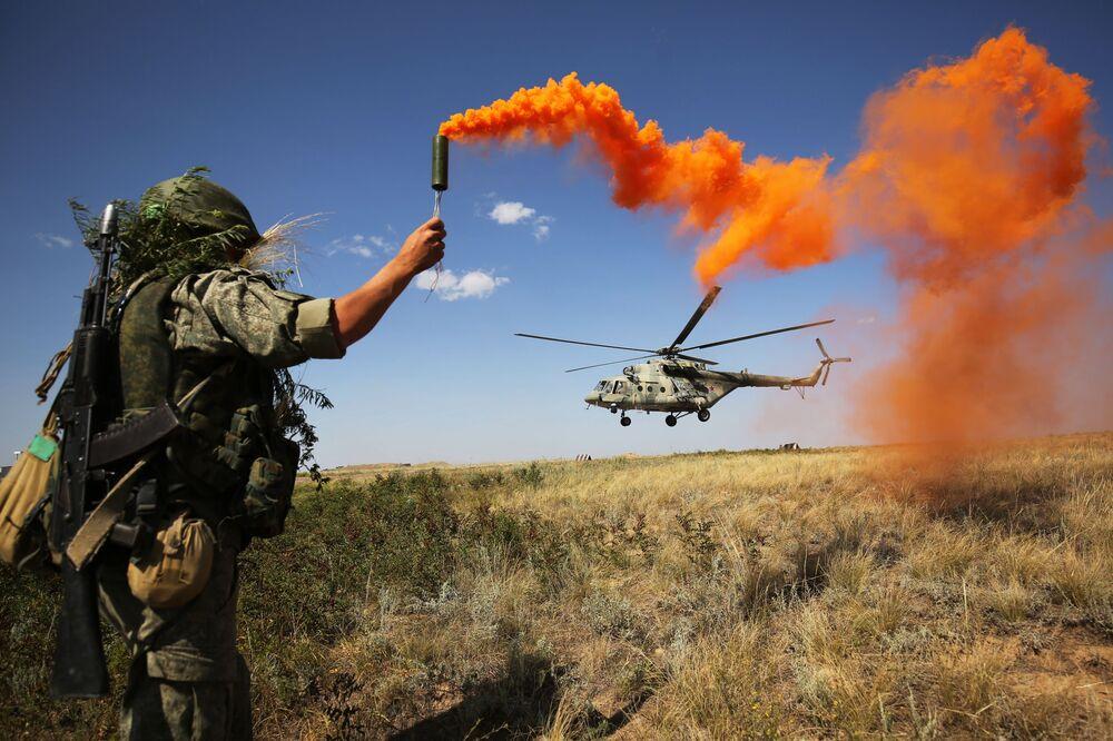 Militar russo participa das manobras táticas do Distrito Militar do Sul no polígono de Prudboi, na região de Volgogrado, junto a um helicóptero militar Mi-8