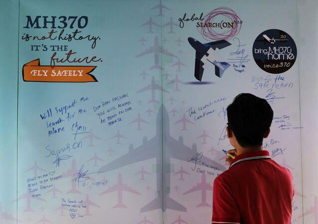 Um homem escreve condolências no Dia da Memória dos trágicos acontecimentos com o avião MH370