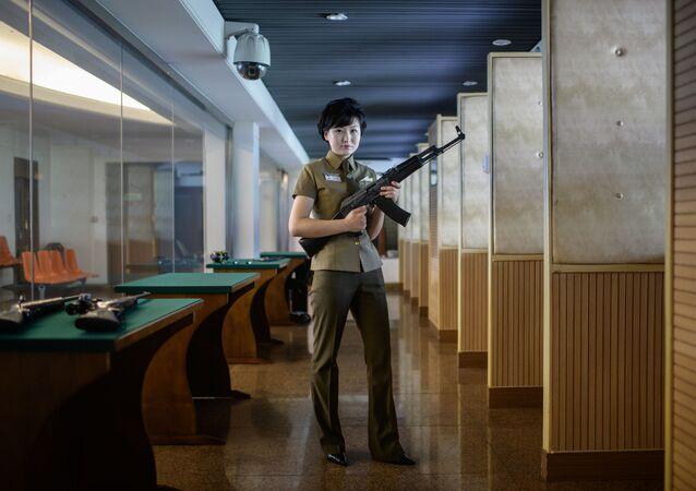 Kim Ju Yang, instrutora de armas de 20 anos de idade, com uma metralhadora de produção norte-coreana em um campo de tiro de Pyongyang