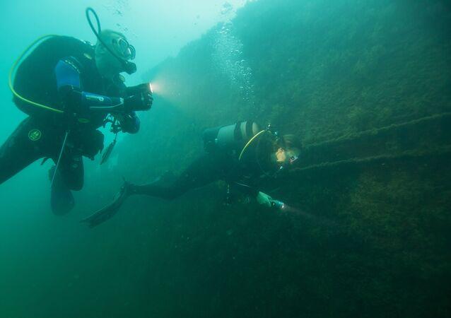 Mergulhadores observando estrutura no fundo do mar (Imagem referencial)