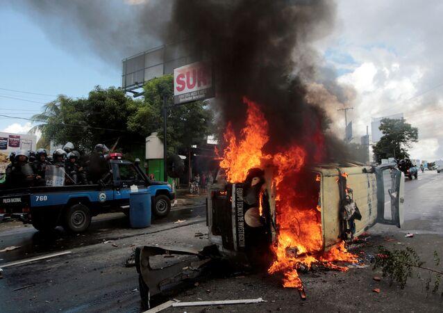 Policiais de choque passam por carro da polícia durante protesto contra o governo do presidente da Nicarágua, Daniel Ortega, na capital, Manágua