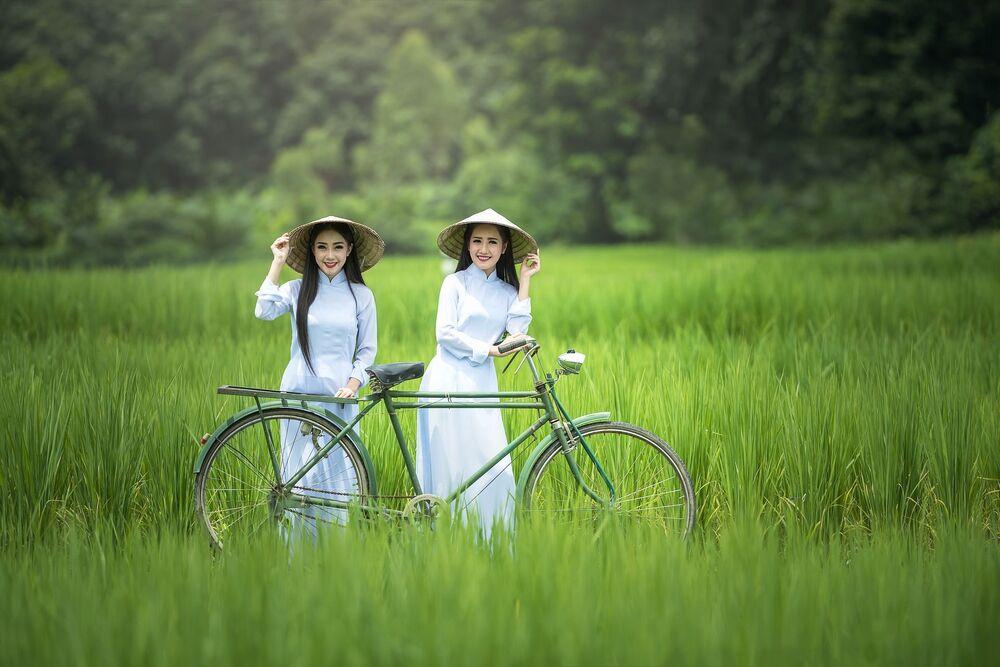 Vietnamitas no campo ao lado de uma bicicleta
